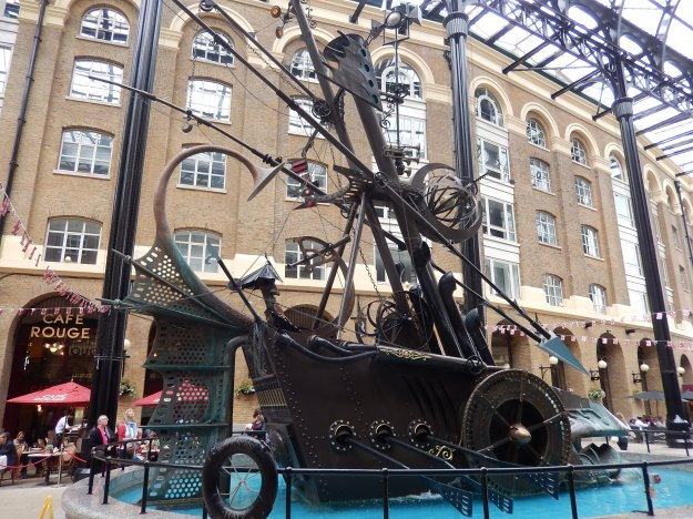 "I loved this Sculpture which decorated a courtyard of a restored warehouse along the Thames east London area. Reminiscent of something from a Jules Verne novel. Part boat, part carriage, made with ""found"" objects such as an old shower head"