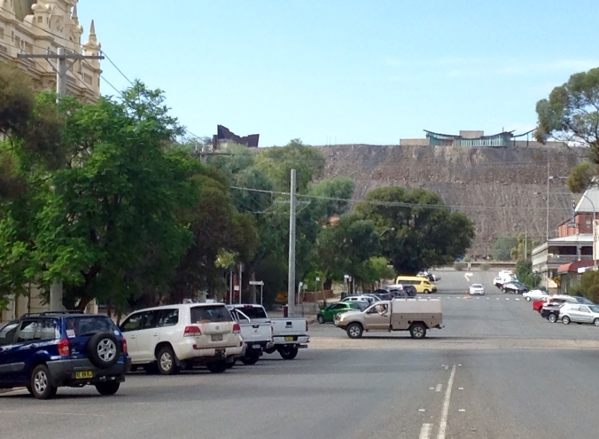 "This photo was snapped quickly as I crossed the street. It demonstrates how Broken Hill is dominated by the slag heap of the ""broken"" hill. The miners' memorial is the building on the top left of the hill"