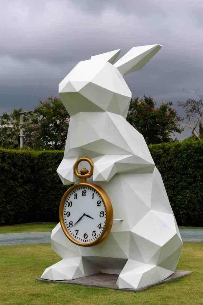 white rabbit holding gold frame pocket watch statue